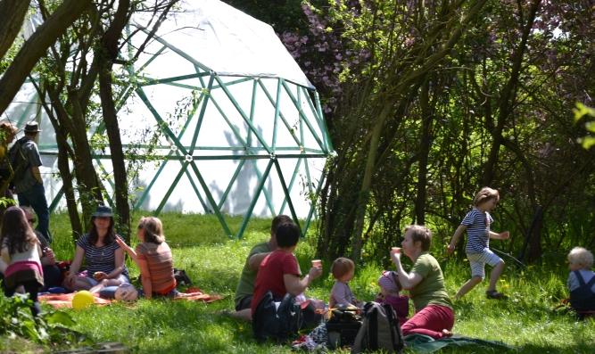 Menschen draußen in der Grünen Spielstadt vor rundem Pavillon