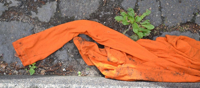 Ein oranges Shirt liegt im Rinnstein.