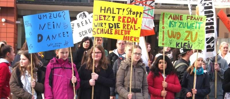 Eltern, Lehrer und Schüler halten Plakate hoch