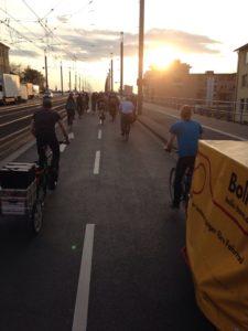 Die Critical Mass mit Fahrradanhängern fährt über die Kennedy Brücke dem Sonnenuntergang entgegen.