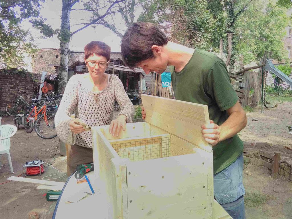 Workshopteilnehmerin und Raphael schrauben die letzten Holzteile zusammen