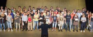 80 Personen auf Theaterbühne vor goldenem Hintergrund