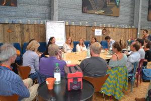 Menschen sitzen um einen Konferenztisch