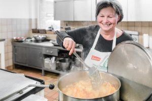 Frau rührt in großem Topf mit Suppe
