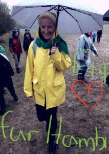Frau mit Regenschirm auf Feldweg