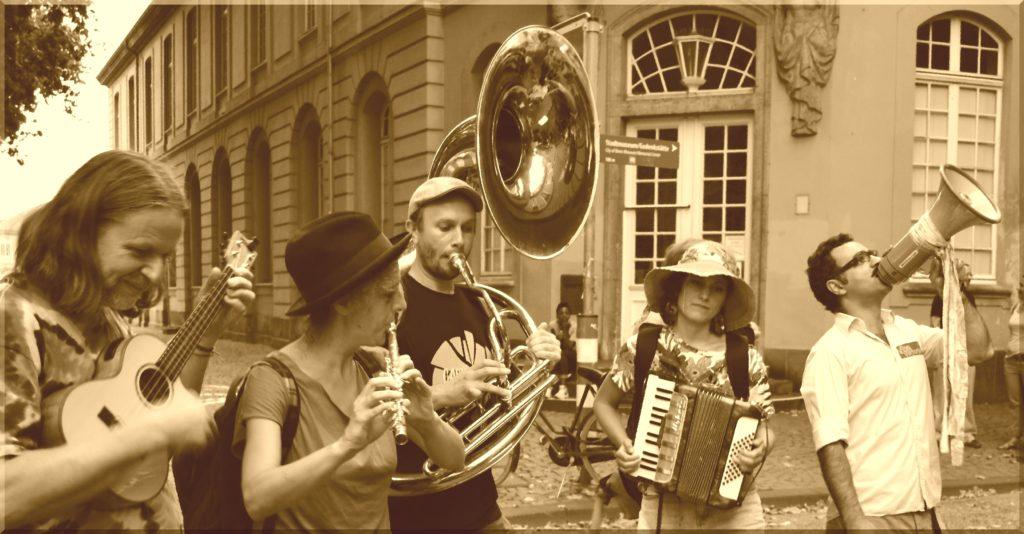 Straßenorchester mit Tuba, Achordeon, Ukulele, Querflöte und Megaphon