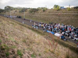 Viele weiß gekleidete Aktivistinnen auf den Gleisen der Hambachbahn, am linken Rand eine weitere Gruppe Aktivisten und Polizei