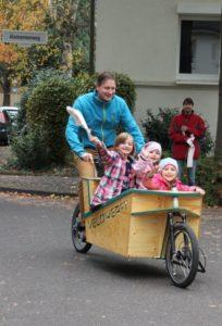 3 Kinder mit Fahne werden im Lastenrad gefahrengefahren