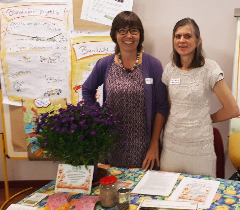 2 Strahlende Blühbotschafterinnen mit Saatgutpäckchen auf einem Tisch vor sich und Pflegeanleitungen auf Plakaten hinter sich