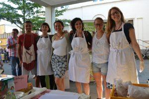 5 junge Frauen und ein Mann mit weißen Kittelschürzen freuen sich über viele Besucher_innen