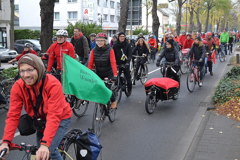 Rot gekleidete Fahrradfahrer_innen, vorneweg Radfahrer m it Bonn grüner Bonn im Wandel Fahne