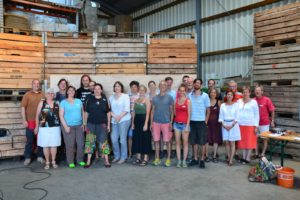 30 Menschen vor Obstkisten in einer großen Lagerhalle