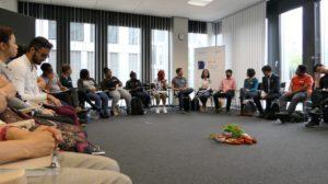 Großer Raum mit 30 internationalen Student*innen im Kreis sitzend