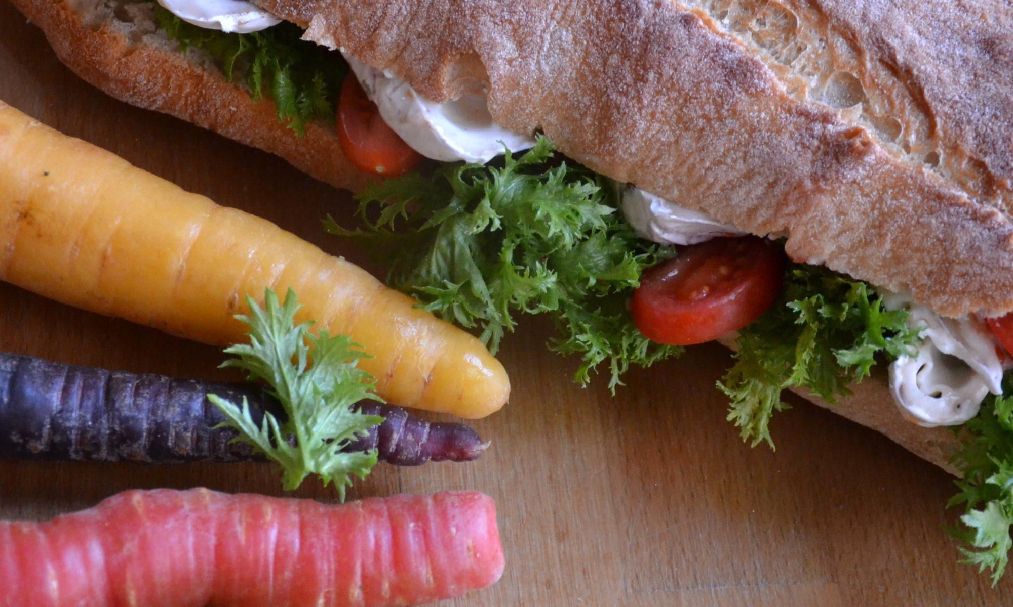 Baguette mit Ziegenkäse, Salat und bunten Möhren