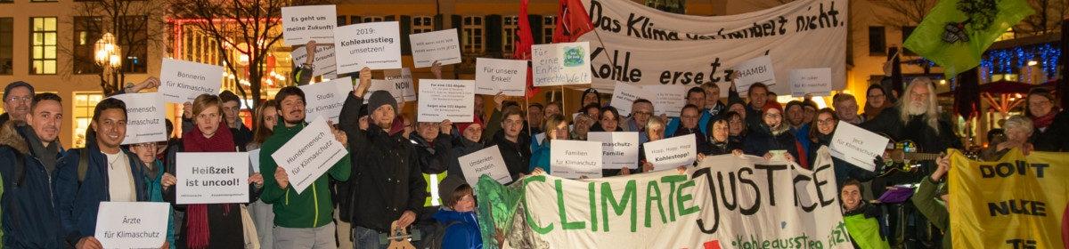Menschen mit Klimaschutztransparenten