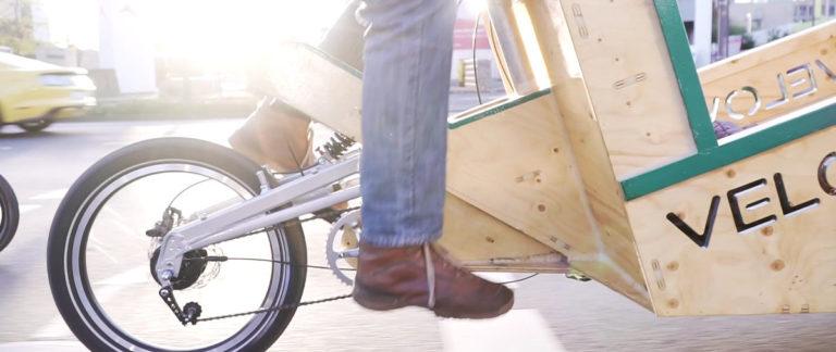 Lastenrad auf der Straße aus Holz von der Seite mit der Sonne im Hintergrund