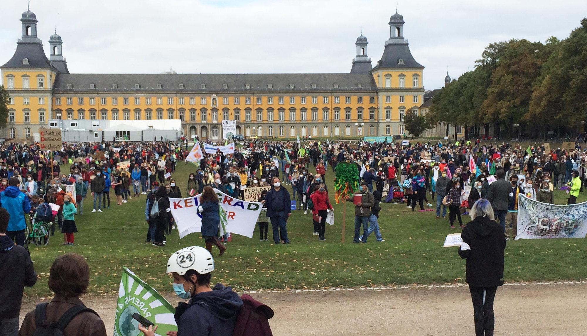 Menschenmenge mit Schildern auf der Wiese, im Hintergrund das Uni Gebäude