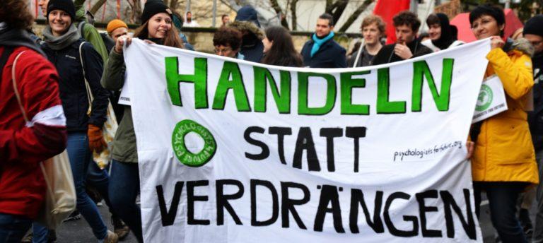 Klimademo-Psychologists4Future tragen ein Banner Handeln statt verdrängen