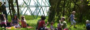 Familien im Gras vor dem Cubus in der Grünen Spielstadt