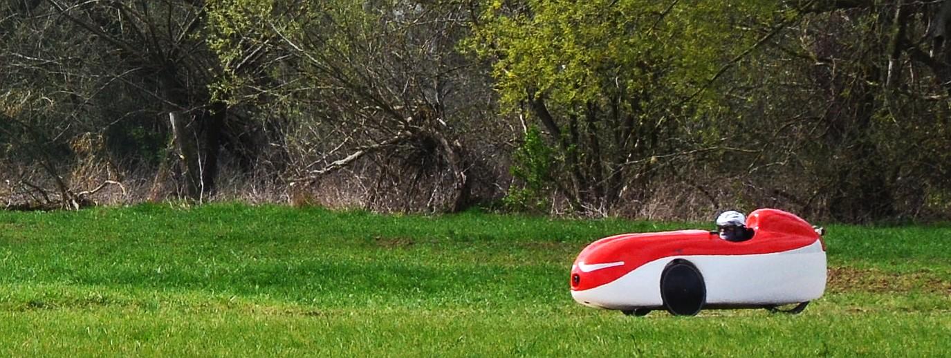 Rotes Velomobil auf Fahrradweg in grüner Wiese