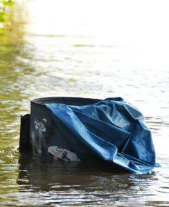Überschwemmte Mülltonne - der Müllsack guckt noch aus dem Wasser