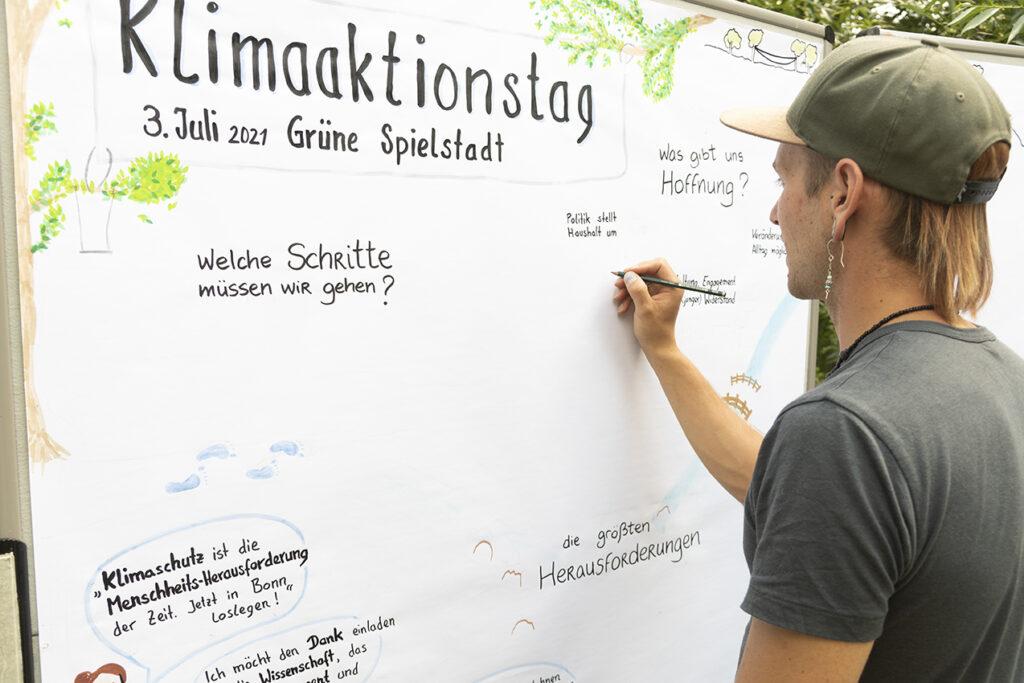 Junger Mann vor großer Plakatwand macht Grafik Recording zum Klimaktionnstag