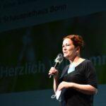 Katja Dörner mit Mikro in der Hand vor einer Power Point Präsentation