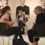 Zwei Personen auf Stühlen, die miteinander sprechen im Hintergrund weitere Personen auf Stühlen. An der Wand im Hintergrund sind große Portraits aufgehängt.