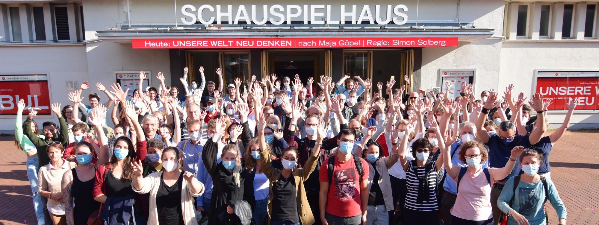 Eine Menschenmenge, die die Hände hebt. Im Hintergrund der Schriftzug des Schauspielhauses.